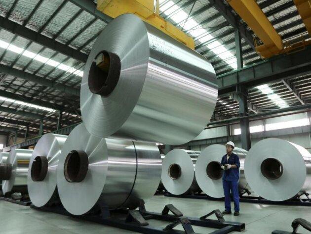 China, Suixi: EinArbeiter platziert in einer Fabrik inder Provinz Anhui mithilfe eines Krans eine Rolle Aluminium in einer Lagerhalle.