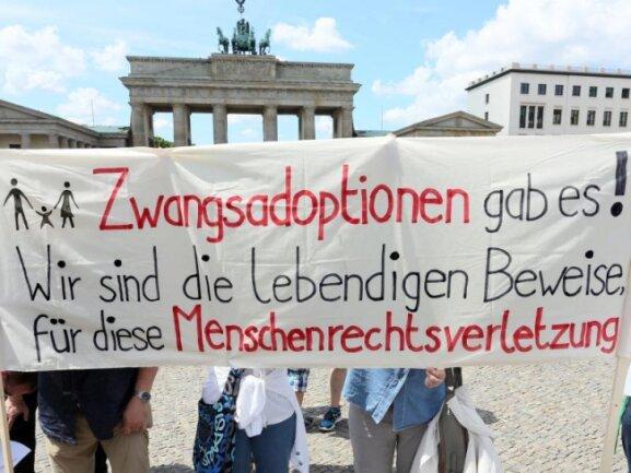 Teilnehmer einer Kundgebung zum Thema Zwangsadoptionen.