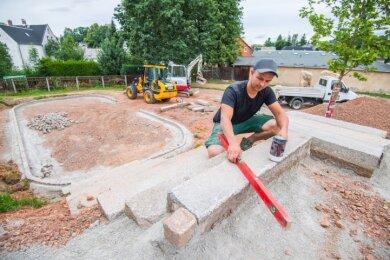 Nachdem es im Vorjahr den Auftakt zur Sanierung des Spielplatzes an der Jahnstraße in Neukirchen gegeben hat, wird jetzt weiter gebaut. Landschaftsgärtner Vincent Einenkel beim Setzen des Aufstiegs zur Hangrutsche und zum Grillplatz.