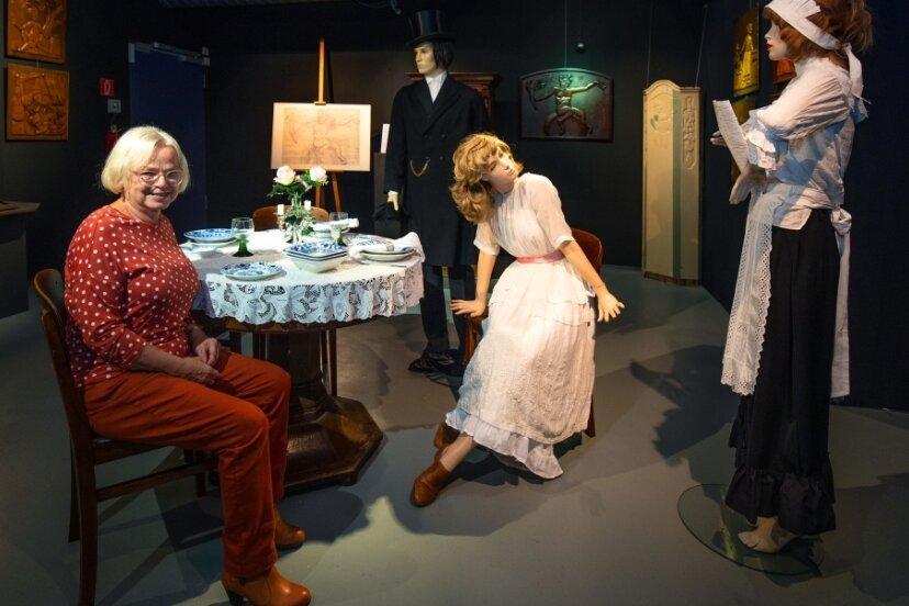 Christina Muschkowski hat die neue Ausstellung im Daetz-Centrum in Lichtenstein mitgestaltet. Hier sitzt sie aneinem Tisch, der mit Puppen umgeben eine Gaststättenszene darstellen soll.