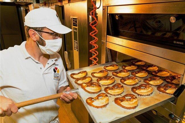 Goldbraun und knusprig: Nach 15 Minuten Backzeit holt Markus Paschel die Brezeln aus dem Ofen.