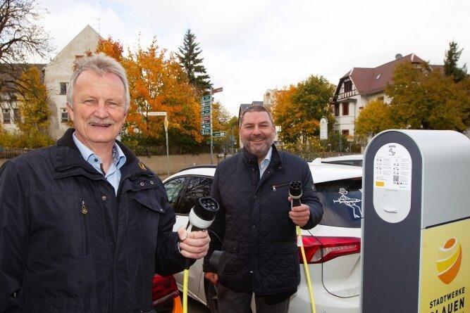 Der Plauener Stadtwerke-Geschäftsführer Peter Kober (links) und Ortsvorsteher Michael Findeisen nahmen am Donnerstag die neue E-Ladesäule auf dem Jößnitzer Wanderparkplatz offiziell in Betrieb.