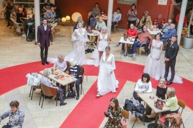 """Neben klassischer Mode wurden beim Fashion Day auch Trends für Hochzeitspaare gezeigt. Vertreter der Agentur """"Die Verheirater"""" schickten dafür Models in Hochzeitskleidern und festlichen Anzügen auf den Laufsteg, der mitten im Eiscafé Bellini im Atrium der Rathaus-Passagen aufgebaut war."""