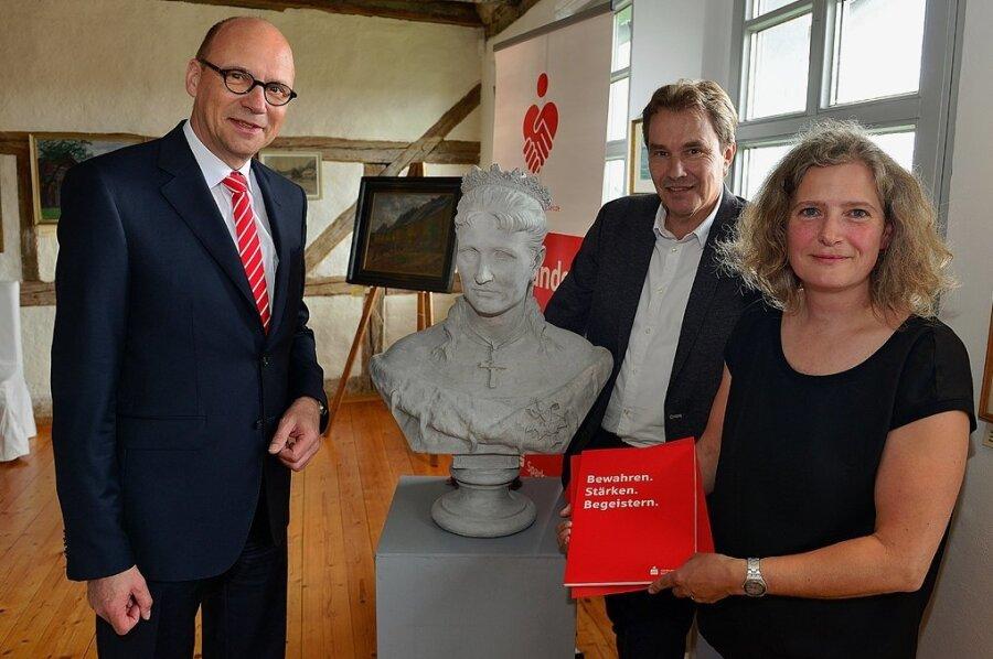 Museumsleiterin Sibylle Karsch, Sparkassenchef Hans-Ferdinand Schramm (l.) und Oberbürgermeister Ralf Schreiber mit der restaurierten Schilling-Büste von Königin Carola und dem Fördermittelbescheid.