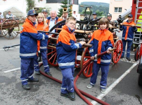 Die Jugendfeuerwehr Falkenau an einer historischen Pferdehanddruckspritze, die die Breitenauer Brandschützer mit zum Feuerwehrfest nach Falkenau brachten.