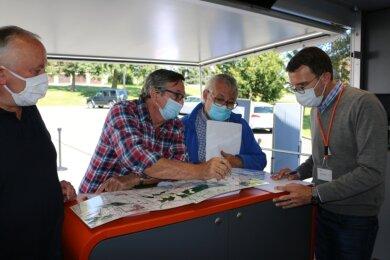 Fachsimpelei am Infobus: Matthias Stark aus Dehles, Joachim Stöhr aus Dröda und Rainer Steger aus Feilitzsch (von links) diskutieren mit Axel Happe von 50 Hertz derzeit geplante Alternativen im Trassenverlauf.
