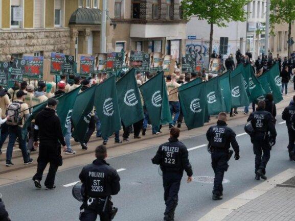 """Teilnehmer eines rechten Aufmarsches der Partei """"Der dritte Weg"""" gehen eine Straße entlang."""