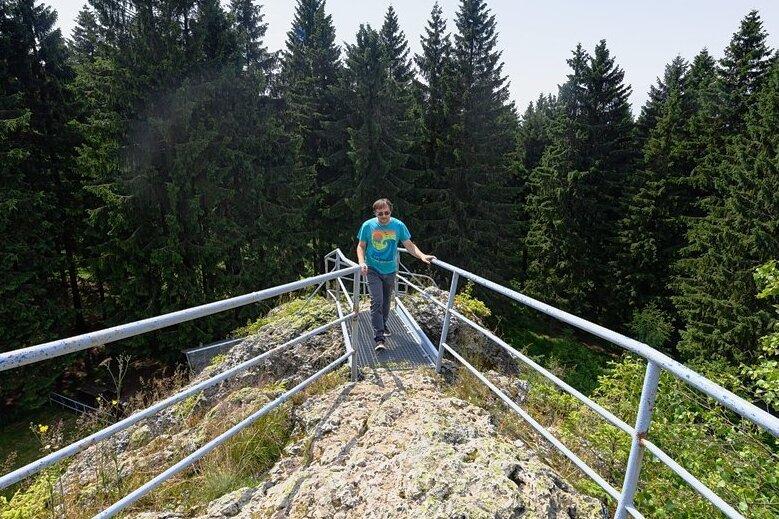 """Dennis Loos, Geschäftsführer des Projekts Geo-Umweltpark Projekts """"Sagenhaftes Vogtland"""", steht auf dem Schneckenstein, dem größten Topasfelsen Europas. Der etwa 23 Meter hohe Felsen im Vogtland wird auch als """"Sächsischer Diamant"""" bezeichnet."""