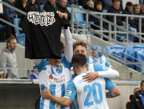 """Daniel Frahn hält nach seinem Treffer zum 3:2 ein T-Shirt mit der Aufschrift """"Support your local hools""""  (""""Unterstützt eure heimischen Hooligans"""") nach oben."""