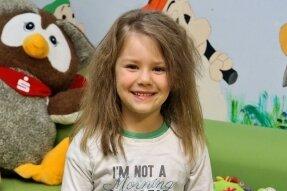Die fünfjährige Emily zeigt das Dankeschön-Plakat der Kinder.