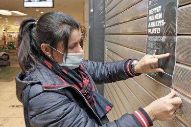Janine Pahlow hängt an dem geschlossenen Geschäft in den Arcaden ein Plakat auf, mit dem sie um Teilnahme an der Petition wirbt.