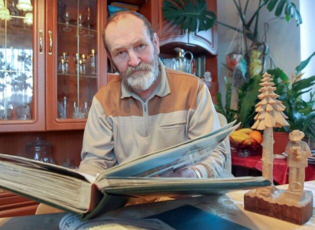 Günter Weigel aus Bad Schlema blättert im Album seines verstorbenen Onkels aus Osnabrück. Im Advent 1982 war dieser auf Besuch im Erzgebirge. Die Weigels erfuhren davon erst jetzt.