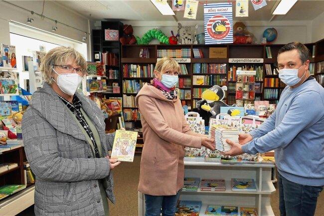 """""""Ich schenk dir eine Geschichte"""" - so lautete am Freitag das Motto des Welttages des Buches, der seit 1995 begangen wird. An der Aktion zur Leseförderung beteiligte sich auch Tom Würker, der am Crimmitschauer Markt seine Buchhandlung betreibt. Für Schulklassen in Crimmitschau, Neukirchen und Werdau stellte er 350 kostenlose Bücher mit dem Titel """"Biber undercover"""" zur Verfügung. """"Mit der Aktion wollen wir bei Kindern und Jugendlichen die Lesefreude wecken und für Bücher begeistern"""", sagte der Buchhändler. Coronabedingt konnte er dieses Jahr keine Klassen in seinem Laden empfangen. Franziska Hofmann (Mitte) vom Julius-Motteler-Gymnasium Crimmitschau holte gemeinsam mit Schulleiterin Karin Penzel das Lesematerial für die Schüler ab.stsu Foto: Thomas Michel"""
