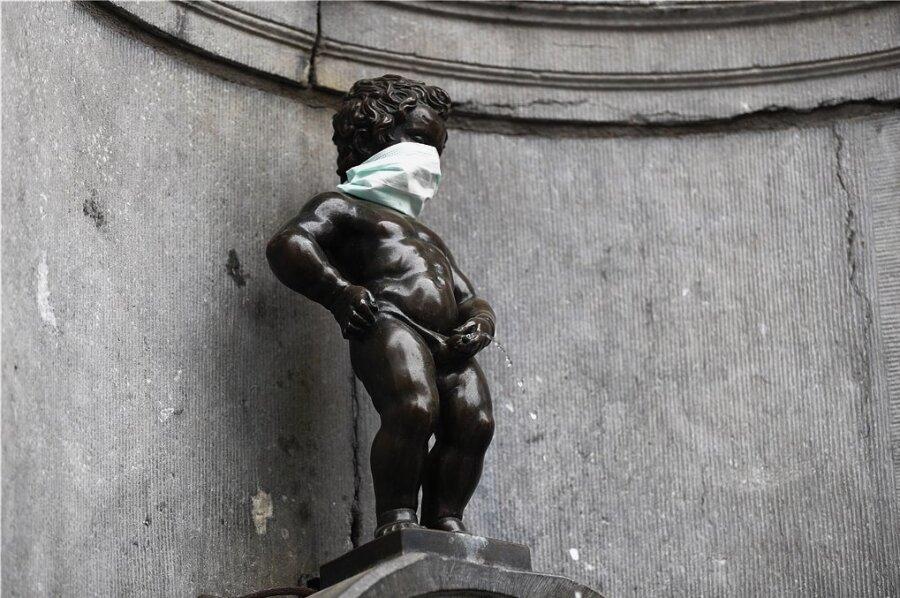 """Überall Krise: Ein Wahrzeichen Brüssels, der """"Manneken Pis"""", trägt einen Mundschutz."""