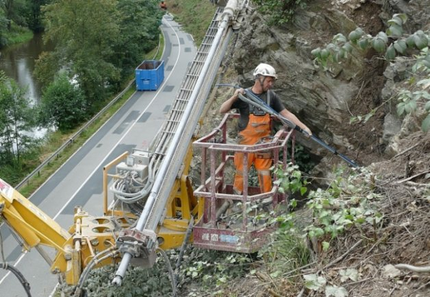 Nachdem Sven Claußnitzer Löcher in die Felsen an der S 288 bei Hopfgarten gebohrt hat, steckt er Anker hinein, an denen der Fangzaun befestigt wird.