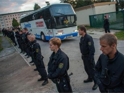 Polizisten stehen vor einem Bus, der Flüchtlinge in eine Notunterkunft bringt.