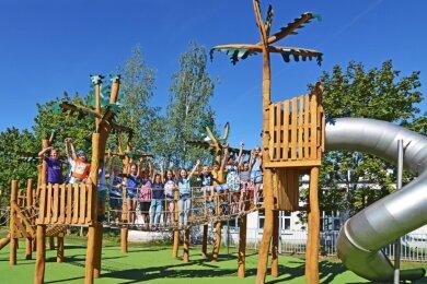 Lugauer Hortkinder haben am Donnerstagvormittag den neuen Stadtspielplatz eingeweiht. Hier stehen sie auf dem Kletterparcours, dessen Gestaltung an die Farne des mehr als 350 Millionen Jahre zurückliegenden Karbonzeitalters erinnern soll.