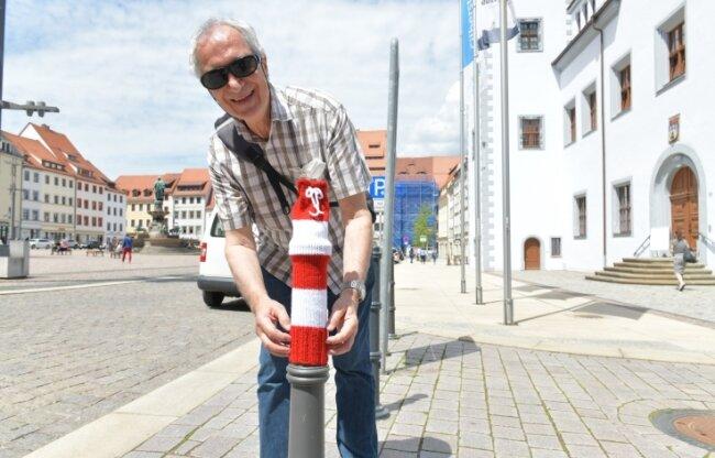 Wolfgang Neuber, Chef der Kreisorganisation Freiberg des Blinden- und Sehbehindertenverbandes, hat probehalber einem Poller auf dem Freiberger Obermarkt eine Mütze aufgesetzt.