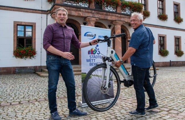 Jürgen Lojewski vom Energieversorger Envia M überreicht dem Rochlitzer Oberbürgermeister Frank Dehne ein Elektro-Fahrrad. Eine Woche lang gilt es nun, so viele Kilometer wie möglich zu erradeln.