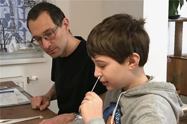 """Der neunjährige Tim führt in Wien unter der Aufsicht seines Vaters einen Corona-Selbsttest durch. Bei den """"Anterio-Nasal-Tests"""" reicht ein einfacher Abstrich mit einem Tupfer im vorderen Nasenbereich."""
