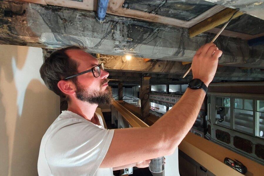 Maler Christian Richter verleiht den erneuerten Balken an der Decke ein historisches Aussehen.