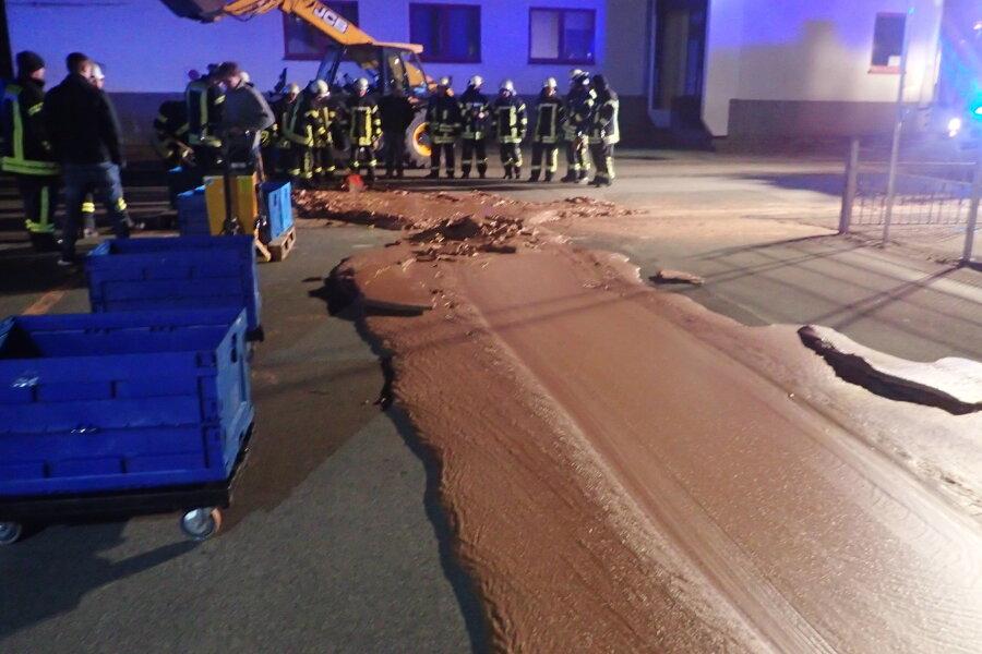 Einsatzkräfte der Feuerwehr stehen neben auf der Strasse ausgelaufener Schokolade. Ein Schokoladentank war bei einer Firma übergelaufen. Die Strasse wurde gesperrt, eine Tonne Schokolade musste von einer Fachfirma beseitigt werden.
