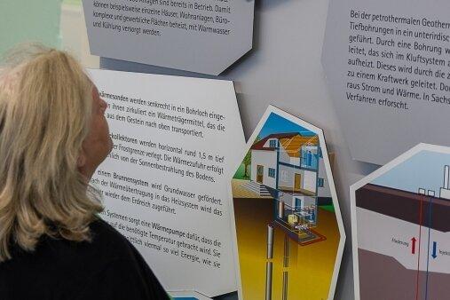 """Maria Faldum vor einem der Plakate in der Ausstellung """"Sachsen hebt seine Schätze"""". Geophysiker Gerd Wolf weist darauf hin, dass Tiefengeothermie und Geothermie unterschiedliche Verfahren sind."""