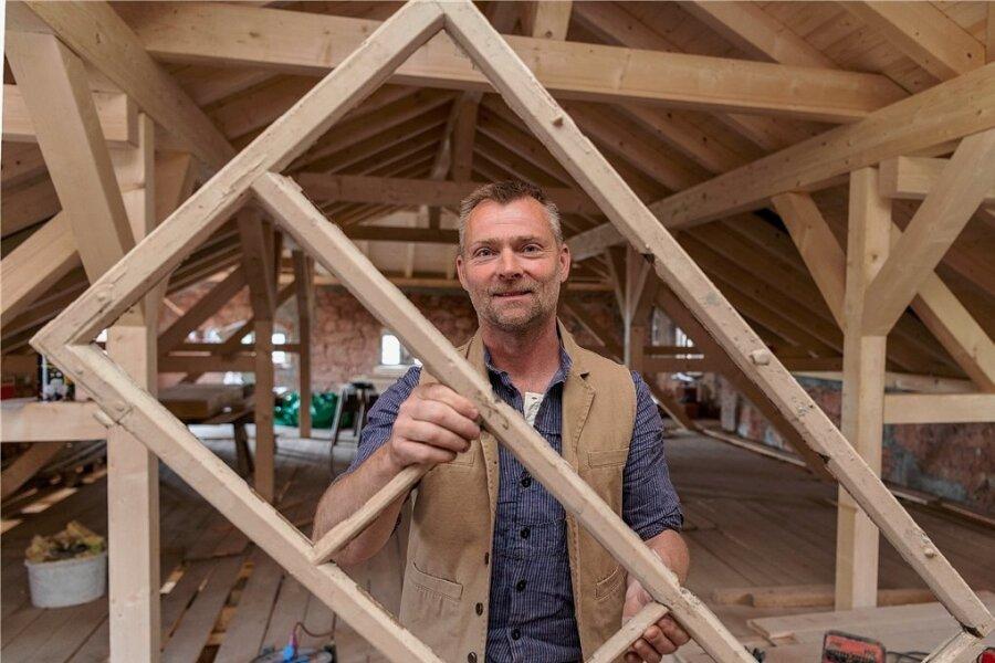 Sebastian Keucher präsentiert einen alten Fensterflügel. Der 50-jährige Dachdeckermeister ließ das marode Dach des Hauptgebäudes bereits neu machen.