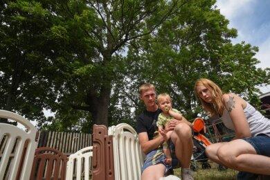 """Fast jeden Tag sind Manuela Haupt, Michael Timmler und ihr zehn Monate alter Sohn Joel in ihrem Garten in der Anlage """"Zur Jahnhöhe"""" in Markersdorf. Doch bei Sturm fürchten sie um Leib und Leben, denn die umliegenden Bäume haben tote Äste, die herunterzufallen drohen."""