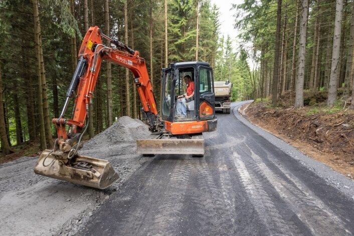 Ein Abschnitt des Bärenfangwegs nahe Oberwiesenthal hat eine neue Asphaltdecke erhalten. Das Foto zeigt Steffen Schreier bei Anpassungsarbeiten zur Anbindung eines anderen Waldwegs.