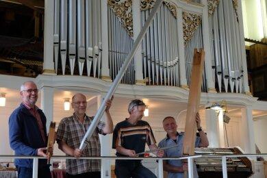 Noch können Pfarrer Christoph Weber, die Orgelbauer Ekkehart Groß und Roland Gotzmann sowie Kirchenvorstand Gerald Anders (von links) mit den ausgebauten Orgelpfeifen der Jehmlich-Orgel posieren. Doch die ersten Prospektpfeifen sind bereits wieder eingebaut.