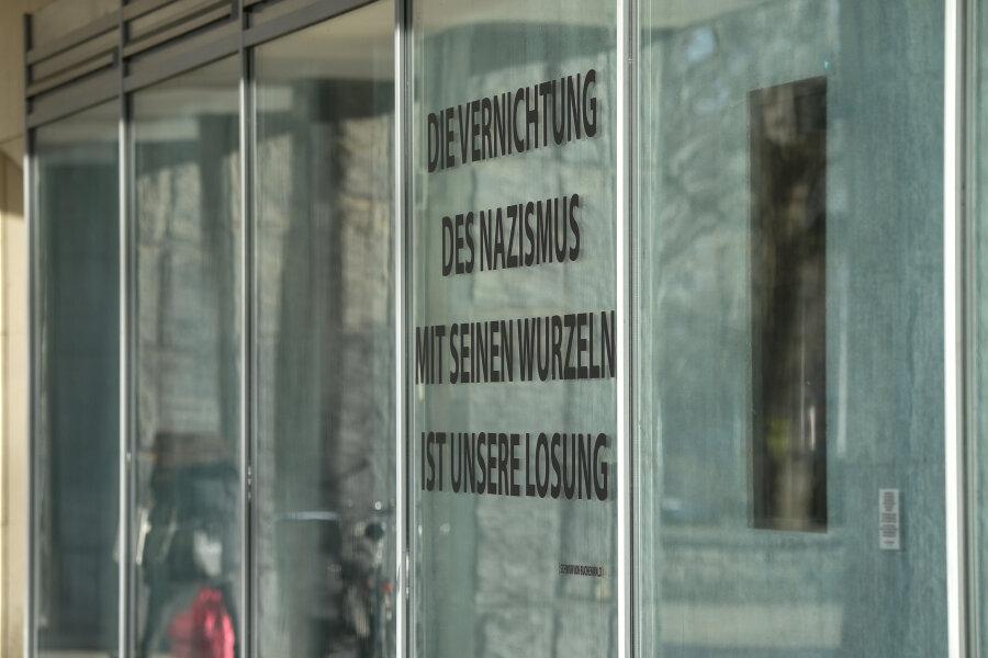 Im Schaufenster eines Ladens im Bürohaus am Marx-Kopf ist eine Glassäule ausgestellt, die offenbar auch Asche von Holocaust-Opfern enthält. Nebenan ist ein Teil des sogenannten Schwures von Buchenwald zu lesen.