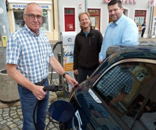 Obwohl es in Zschopau wie hier am Markt bereits Ladesäulen gibt, machen sich Peter Uhlig (CDU), Niels Sigmund (Grüne) und David Kessmann (Wir - Die Vereine/v. l.) für eine schnellere Form des Ladens stark. Gemeinsam erarbeiteten die drei Fraktionen einen Antrag, der Anklang fand.