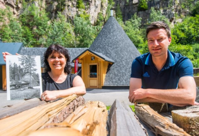 Mira Thiele und Michael Then vor dem neuen Köhlerimbiss in der Schauköhlerei an der Talsperre Sosa. Mira Thiele hält eine Zeichnung der alten Meiler-Gaststätte, die sich einige hundert Meter entfernt befand.