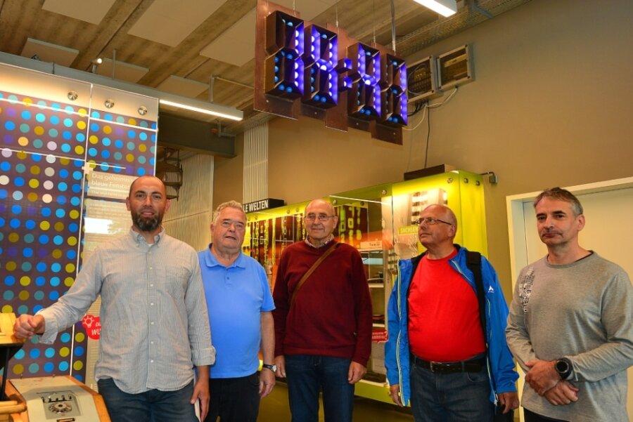 Museumsleiter Tobias U. Müller, Reiner Fucik und Gotthard Lehn vom früheren Uhrenwerk sowie die Helfer Joachim Graubner und Ronald Schuhmann (v. l.) vor der Digitaluhr im Museum Zeit-Werk-Stadt.