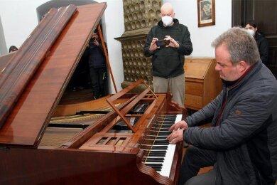 Klavierbaumeister Holger Hofmann spielt das erste Mal im Biedermeier-Zimmer auf dem restaurierten Hammerflügel. Schlossleiter Andreas Quermann nimmt alles mit seinem Handy auf.