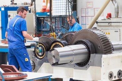 Flender gehört zu den Weltmarktführern für Industrie und Windgetriebe: Am Standort Voerde in Nordrhein-Westfalen montieren zwei Flender-Mitarbeiter die Verzahnungsteile eines Stirnradgetriebes.