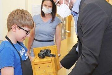 Christiano aus der vierten Klasse überreicht Kultusminister Christian Piwarz, hier mit Susan Leithoff, einen Nistkasten.
