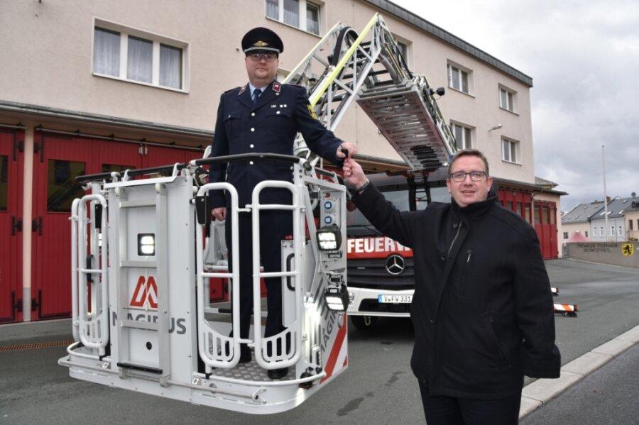 Oberbürgermeister Mario Horn übergibt an Daniel Bauer, Ortswehrleiter der Freiwilligen Feuerwehr Oelsnitz, den Schlüssel für das neue Fahrzeug mit der Drehleiter.