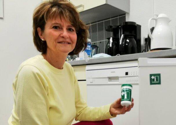 Am Kühlschrank klebt ein Sticker mit Hinweis auf die Notfalldose. Sozialamtsleiterin Cornelia Utech zeigt den kleinen Lebensretter.