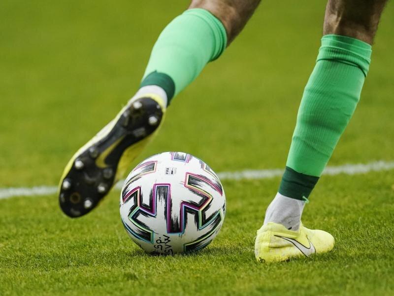 Ein Fußballspieler spielt den Ball.