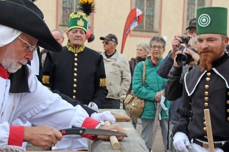 Frank Noack (l.) beweist beim Freiberger Herbstfest auf dem Untermarkt sein Geschick beim Sägen während des Bergmeisterpokals. Andy Franke (r.) hat ein waches Auge darauf, dass alles korrekt abläuft.