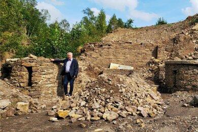 Reste des alten Freibads. Frank Riedel steht vor der Säule, die zusammen mit der Mauer im Hintergrund und dem Nixen-Podest erhalten werden sollen. Die Säule rechts wird wieder unter Erdmassen verschwinden.
