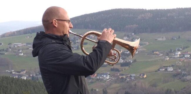 Mit einem von Philip Josiger aus Scheibenberg extra für ihn angefertigten Flügelhorn musiziert Jan Giera auf einem Felsen bei Rittersgrün.