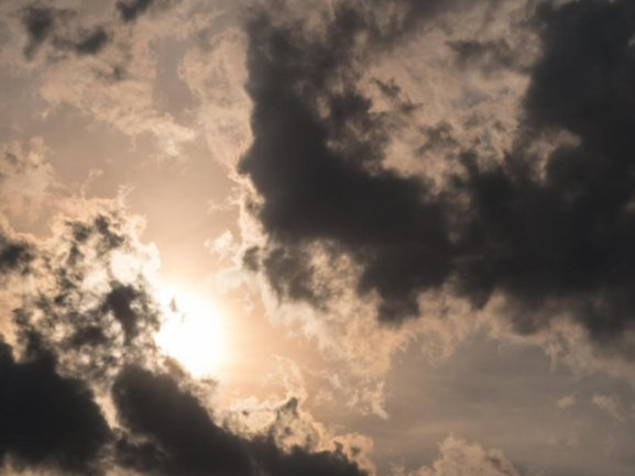 Die Sonne scheint hinter dunklen Wolken.