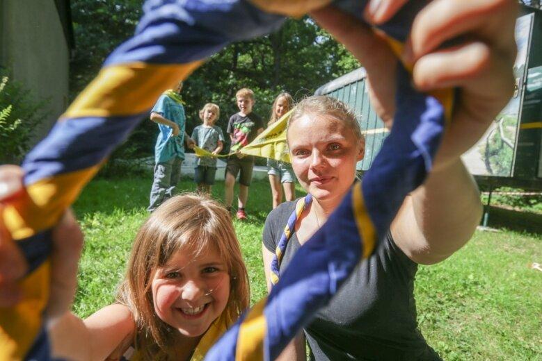 Die achtjährige Alyson und Franziska Baer, die Mitbegründerin der Chemnitzer Gruppe, zeigen eines der blau-gelben Halstücher, das Mitglieder mit Ablegen der Prüfung bekommen. Im Hintergrund steht der neue Bauwagen der jungen Fährtenleser.