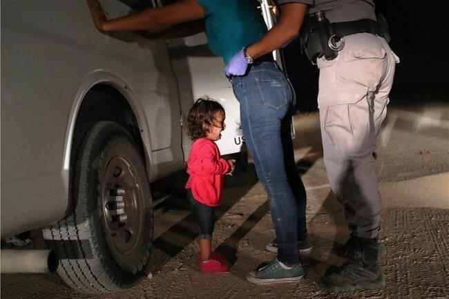 Dieses Foto wurde inzwischen zum Sinnbild von Donald Trumps Null-Toleranz-Politik an der texanisch-mexikanischen Grenze. Zu sehen ist ein schreiendes Mädchen neben ihrer Mutter. Der Fotograf John Moore nahm es auf, während die Grenzer die Frau aus Honduras nach ihrer Festnahme durchsuchten.