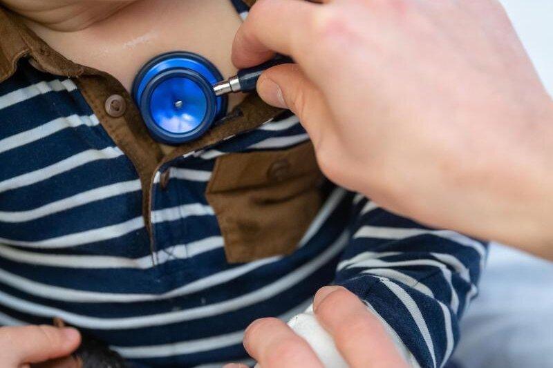 Ein Arzt untersucht ein Kind mit einemStethoskop.