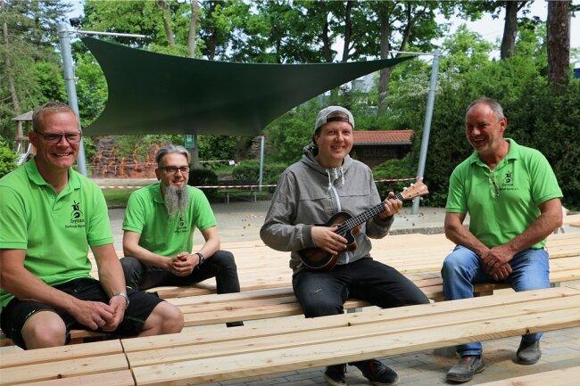 Thomas Wagner, Mario Branse, Musiker Christian Wenzel und Falk Zeh (von links), Vorsitzender vom Syrauer Dorfclub-Verein, auf den neuen Sitzbänken der Freilichtbühne.