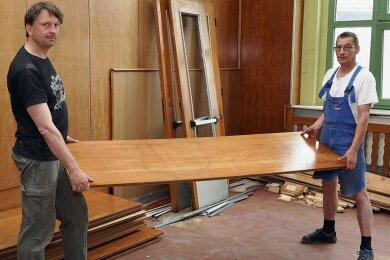 """Christoph Kopp (links) und Jens-Uwe Dietze vom Verein """"Wir in Werdau Süd"""" demontieren die hölzerne Wandverkleidung aus dem einstigen Mitropa-Saal."""
